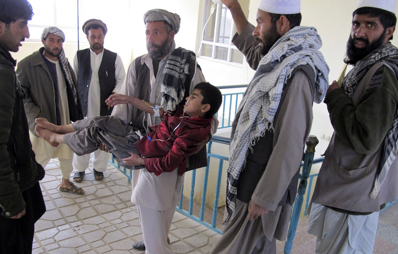 An Afghan man carries a boy who was wounded in an explosion in Kunduz, Afghanistan, on Saturday. Ten people including three children died in the attack.