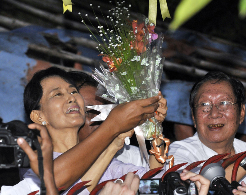 Pro-democracy leader Aung San Suu Kyi smiles after she received flowers from supporters at the gate of her home Saturday in Yangon, Myanmar. Myanmar's military government freed her after her latest term of detention expired.
