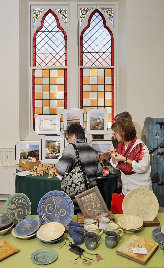 Colleen Boland, right, helps customers looking at her collection of items from Ireland at the craft fair.