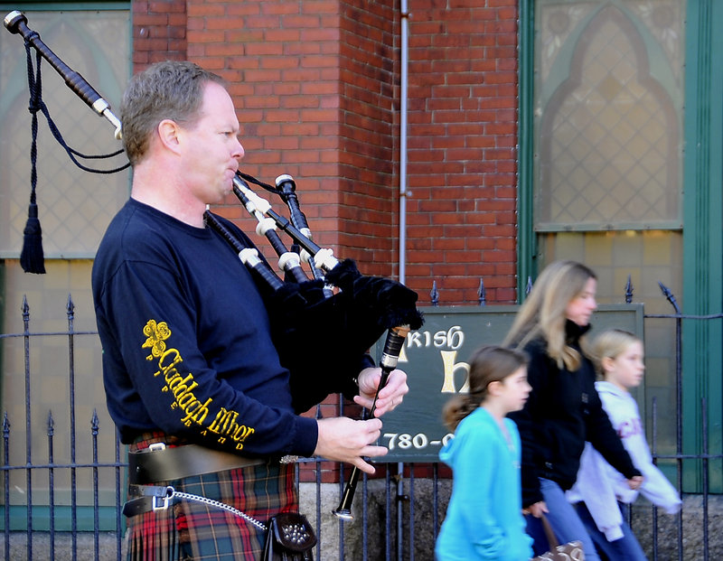 Tom Ryan plays bagpipes as Catherine Cornell and daughters Caitlin, 9, left, and Anna, 7, all from Cape Elizabeth, head into A Celtic Christmas, a craft fair at the Irish Heritage Center.