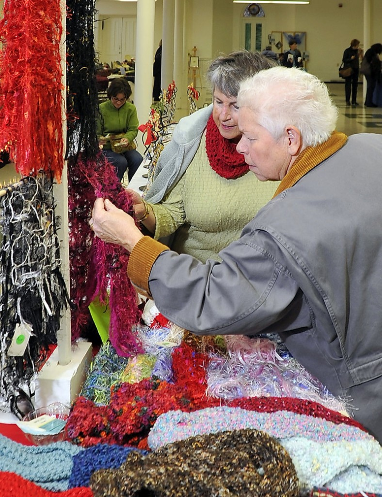 "Rita Thompson of South Portland, right, inspects the handcrafted ""Magic Laces"" and Mobius cowls made by artist Jean Maiorano, left, at the craft fair."
