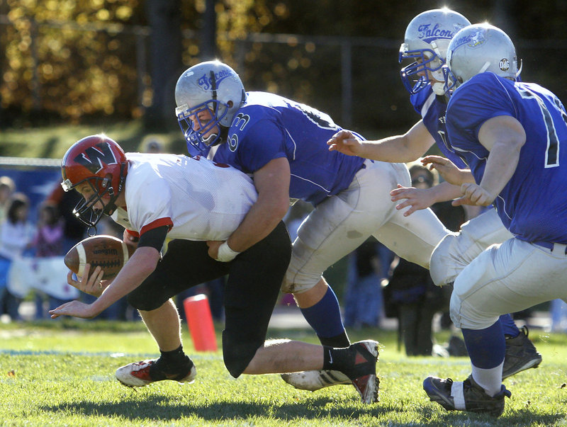 Wells quarterback Paul McDonough was the target of Mountain Valley's swarming defense throughout the Western Class B championship game Saturday at Rumford. Ryan Glover applies the hit – one of the five sacks that the Falcons leveled on McDonough.