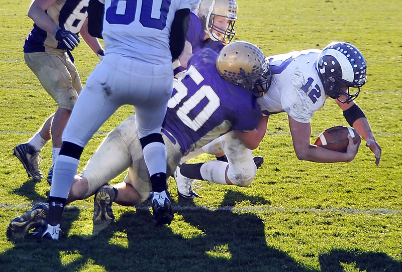 Cheverus linebacker Zach Dulac takes down Deering quarterback Jamie Ross during a thrilling Western Class A final at Cheverus on Saturday. The Stags won, 35-34.