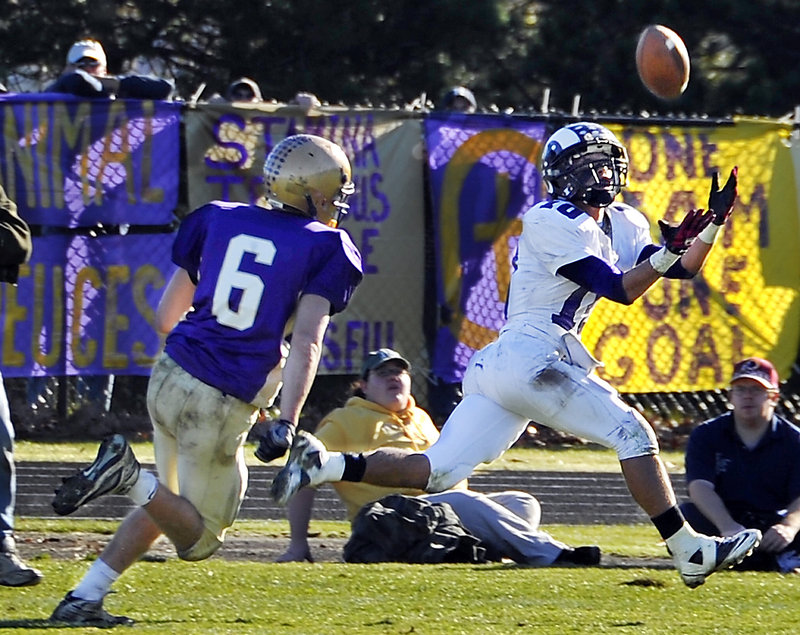 Renaldo Lowry of Deering hauls in a pass from Jamie Ross, behind Peter Gwilym of Cheverus. The play turned into a 60-yard touchdown.