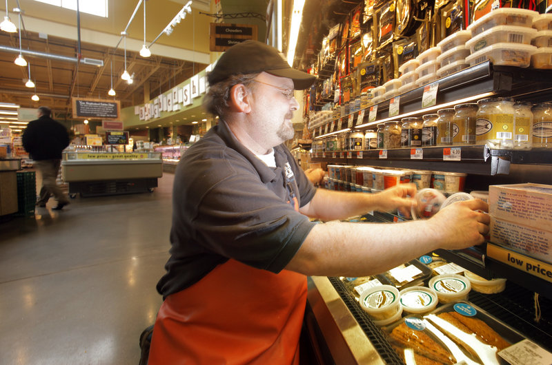 Eric Cook, a seafood associate team leader at Whole Foods Market in Portland, stocks fresh crabmeat processed by The Atlantic Red Crab Co., which Jon Williams opened last year.