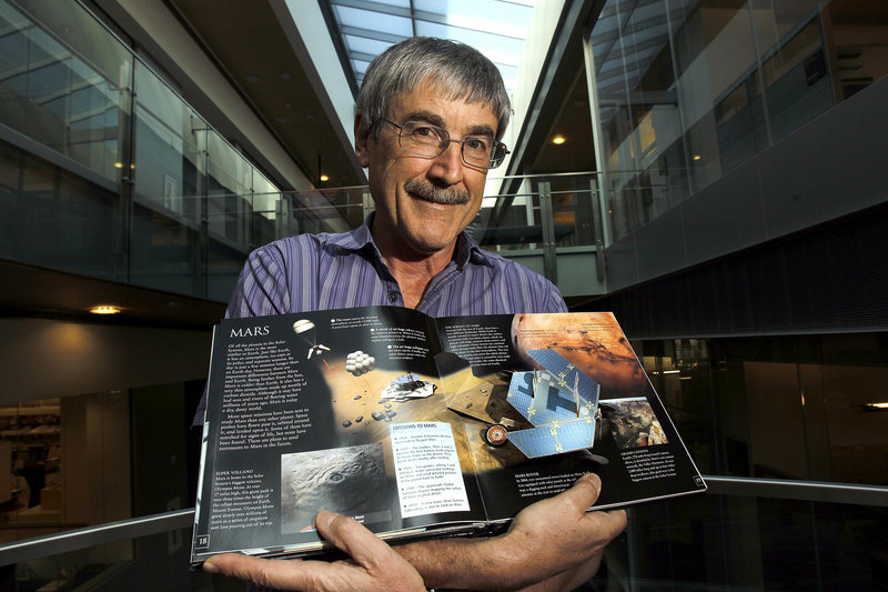 Dr. Paul Davies of Arizona State University holds a book on Mars as he stands in the atrium of the Biodesign Institute building on the ASU campus.