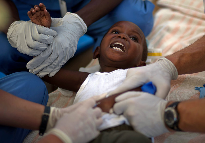 A child with cholera symptoms is treated Monday by volunteer American doctors at a hospital in Archaie, Haiti. Nearly 1,000 people have been killed and more than 16,000 have been hospitalized for cholera across the nation.