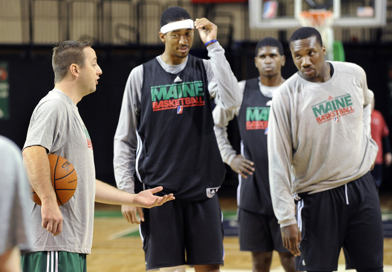 Coach Austin Ainge, left, talks to Magnum Rolle, Eugene Spates and Tiny Gallon during the Red Claws practice Tuesday at the Portland Expo. The Red Claws will be younger this season than the mostly veteran team that went 27-23 in the franchise s inaugural season.