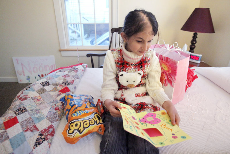 Noora Afif Abdulhameed looks at a card she opened after arriving in her room at the Ronald McDonald House on Wednesday. The Iraqi girl returned to Portland to have further reconstructive surgery on her scalp.