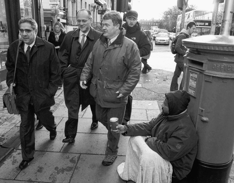 Ajai Chopra, left, deputy director of the European Department of the IMF, walks with several colleagues past a man begging on the street as they head to the Central Bank of Ireland for talks with the Irish government in Dublin on Thursday.