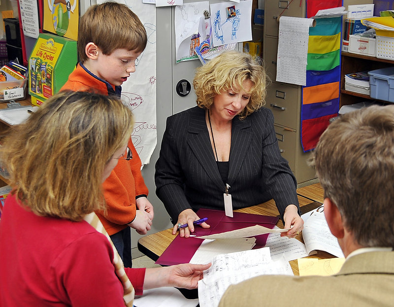 Margaret and Fritz Hansen discuss their son Peter's writings with his second-grade teacher, Pamela Ridley, during parent-teacher conference time at Prides Corner School in Westbrook on Thursday.