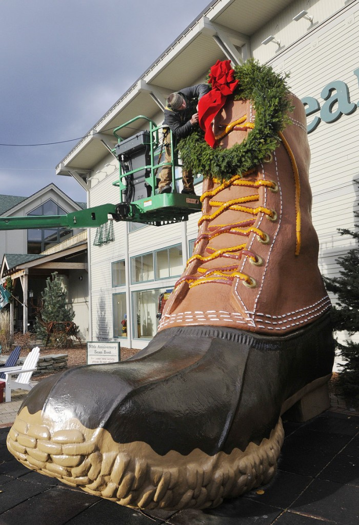 Jesse LaCasse of Pandora LaCasse Design puts up a wreath on the boot during the L.L. Bean Northern Light Celebration in Freeport Saturday.
