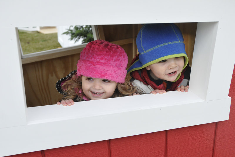 Emily Nicoll, 2, of Fredericton, New Brunswick, and Declan Byrne, 2, of Hartford, Conn., peek out the window of a crooked wooden house during the Northern Light Celebration.