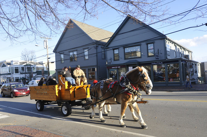 Bells jingle as a pair of Belgians from Meadow Creek Farm pull a wagonful of passengers down Freeport's Main Street on Saturday.