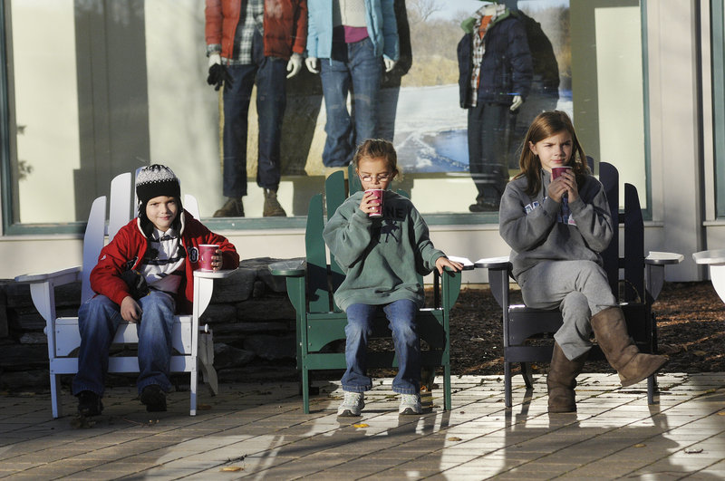 From left, Daniel Forester, 8, Christina Forester, 7, and Stephanie Forester, 11, all of Walpole, Mass., enjoy free hot cocoa as they sit in Adirondack chairs outside L.L. Bean during the Northern Light Celebration Saturday.
