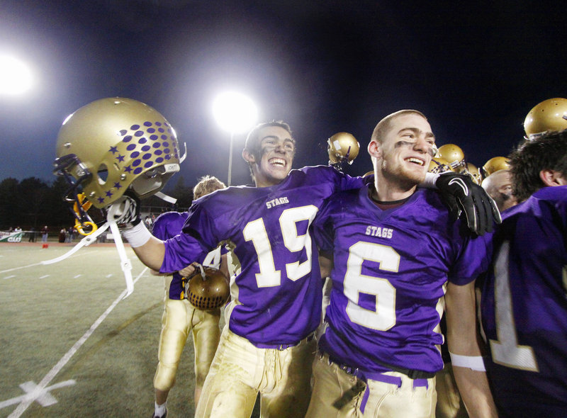 Cheverus High School's undefeated Stags, including an elated Louie DiStasio, left, and Peter Gwilym, celebrate another victory Saturday, grabbing the Class A state championship over Bangor, 46-8.