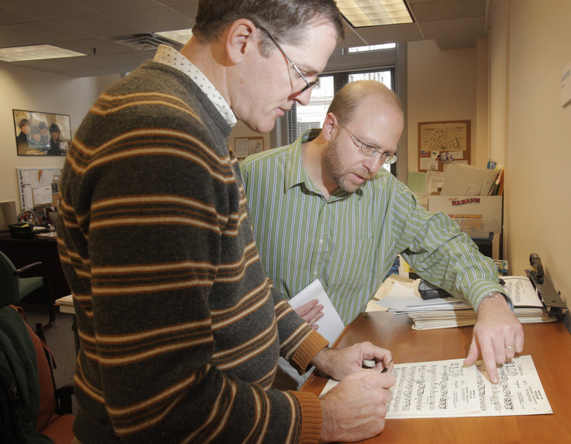 Reporter Ray Routhier looks over sheet music with Jon Poupore, left, librarian for the Portland Symphony Orchestra.