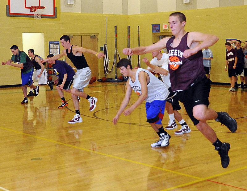 Caleb King, right, leads candidates for Greely's boys' basketball teams through an agility drill during the first day of official team practice Monday in Cumberland.