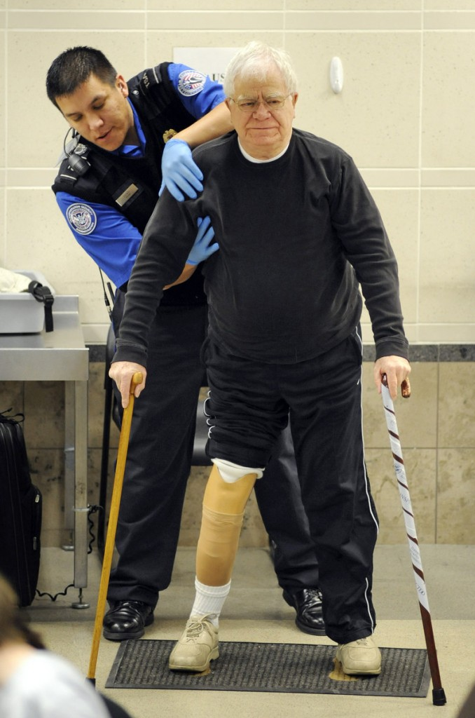 A TSA officer pats down a traveler as he works his way through security at the Minneapolis-St. Paul International Airport in Bloomington, Minn., Wednesday. Around the country, most travelers selected for full-body scans or pat-downs chose to submit rather than disrupt the security procedures on one of the most heavily traveled days of the year.