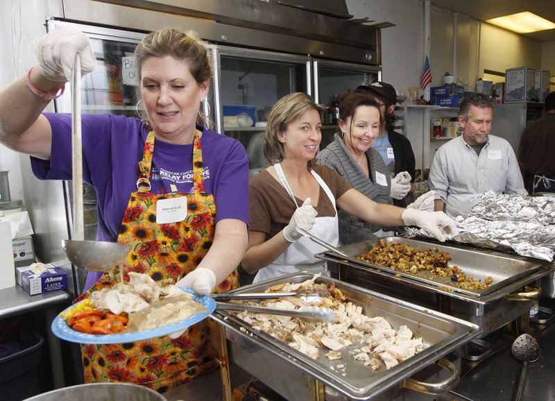 Deborah Scott of Porter serves up a heaping dish of food at the Portland Club, where the United Way of Greater Portland sponsored a community dinner on Thanksgiving Day.