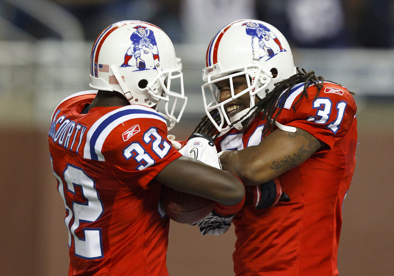 Devin McCourty, left, and Brandon Meriweather celebrate after one of McCourty's two interceptions Thursday in the Patriots' win against the Lions.