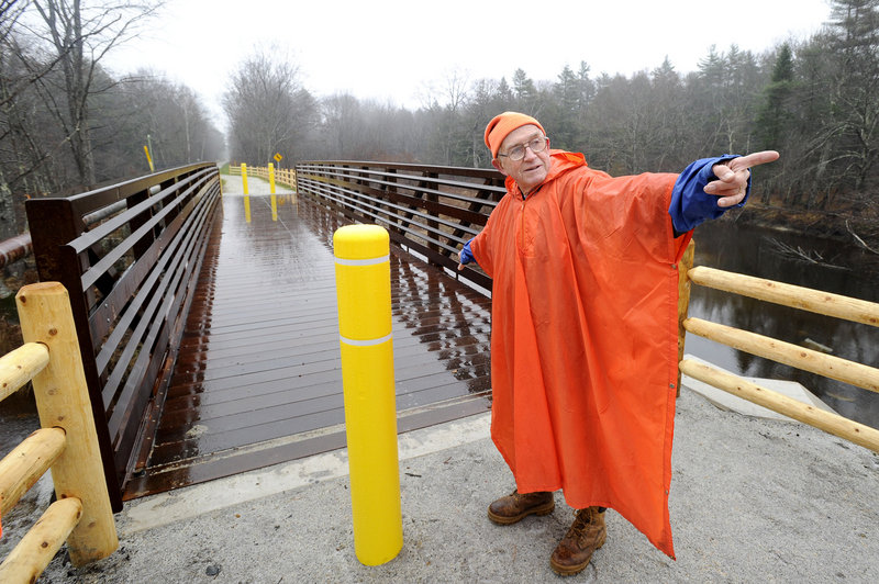 John Andrews points toward Kennebunk as he shows off a new section of the Eastern Trail in Arundel where it crosses the Kennebunk River with a new bridge. The trail is part of the 3,000-mile East Coast Greenway.