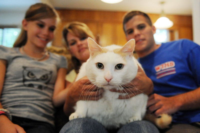 Donna Damiani, center, and her children Melissa, left, 12, and Vince, 17, hold their cat, Prince Chunk, at home in Washington Township, N.J., in 2008. The enormous cat, who became famous when found wandering in a South Jersey town after his owner lost her home to foreclosure, has died. He was about 10.