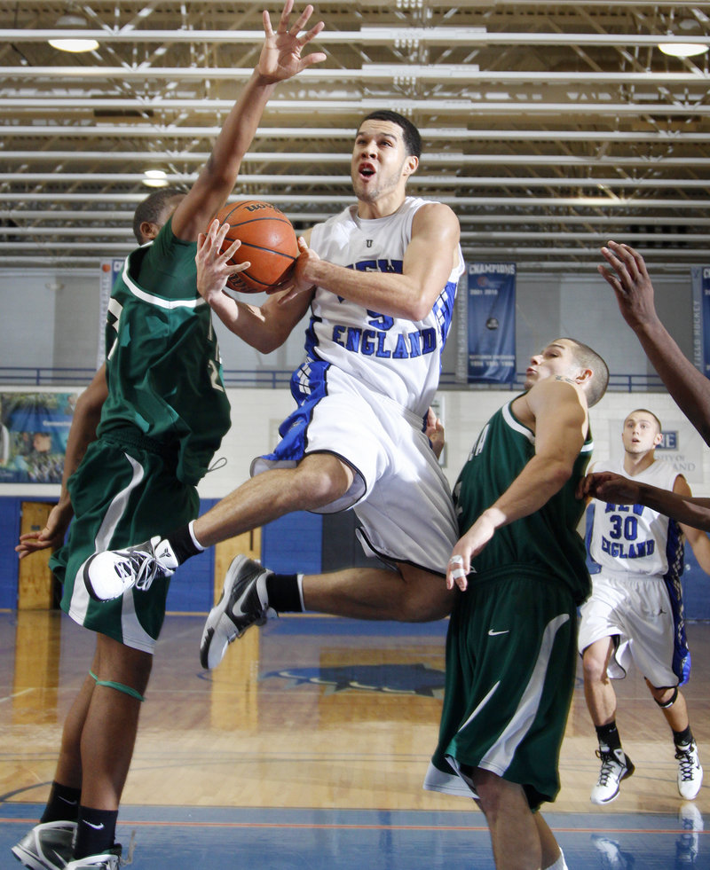 Chad Rentrope of the University of New England slices to the basket between Mount Ida's Jeffrey McNair, left, and Joe Cabral during Saturday's game at Biddeford. Rentrope had 18 points as UNE got its first victory of the season.