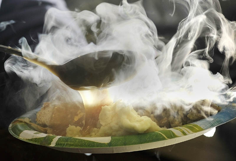 Steam rises as gravy is poured over a plate of turkey being served up during a special Thanksgiving lunch on Wednesday at Highland Avenue Terrace in Gardiner.