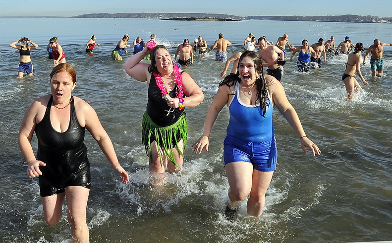 Stacie Haines, left, Beth Dimond and Elisa Doucette scurry from the water as fast as they went in Friday after realizing how cold the water was during the Natural Resources Council Polar Bear Plunge at East End Beach in Portland.