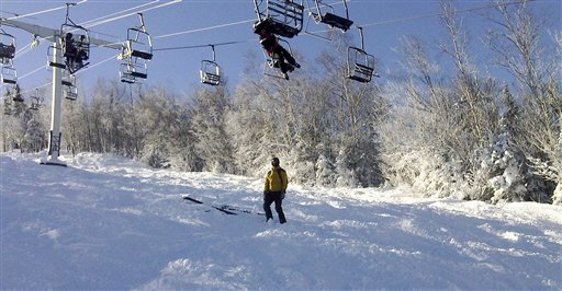 A skier tries to climb down from a stalled ski lift chair Tuesday.