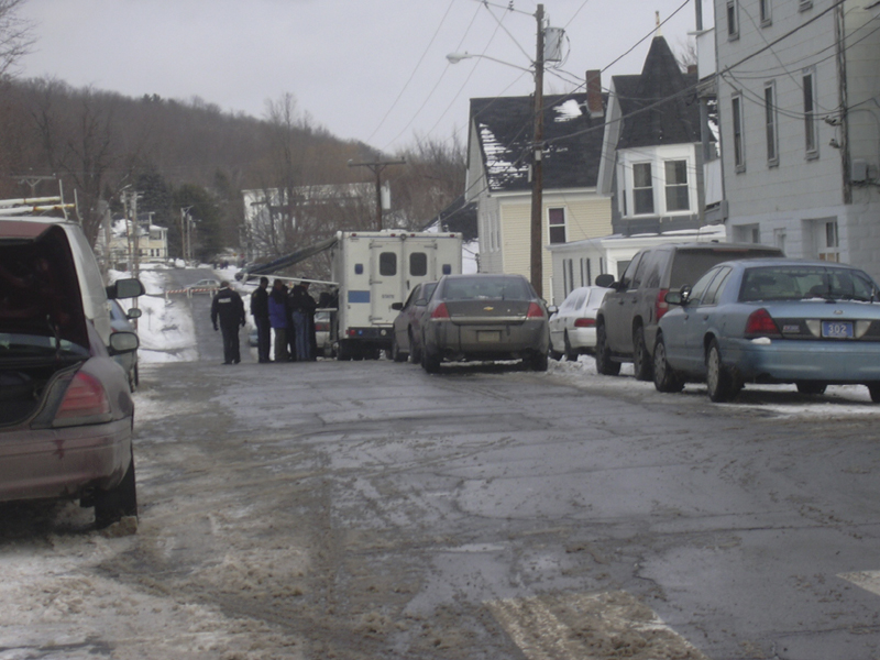 Members of the Maine State Police tactical squad confer outside 37 Washington St. this morning in the city's Sand Hill neighborhood. Sources said the activity is part of the investigation into the slaying of Paul A. Allen, 47, of Augusta.