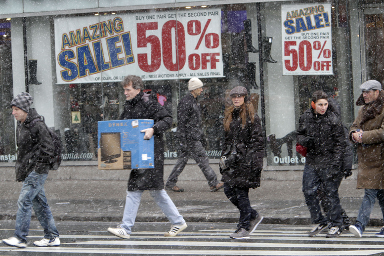 Shoppers make their way in the snow in Union Square today in New York.