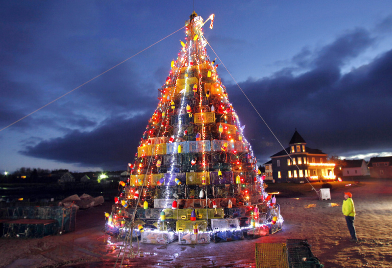 Albert Carver, looks at a 50-foot-tall Christmas tree made of lobster traps on Beals Island, Maine. Some of the top lobster-fishing ports in New England are claiming bragging rights about who has the biggest and best Christmas tree created from lobster traps. The groups that put up the trees say they draw attention to the ports' maritime heritage, bring people together and raise money for good causes. The tree in Beals helps raises money for the Beals-Jonesport Fourth of July festivities and the one in Gloucester benefits a nonprofit devoted to the arts.