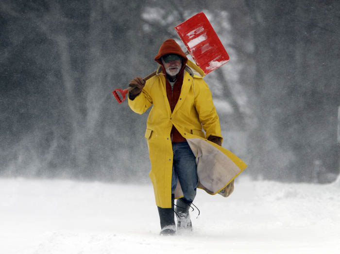 Snow swirls around Leo Picone, of Brunswick, Maine, as he makes his way along a road in Brunswick to shovel out customers.