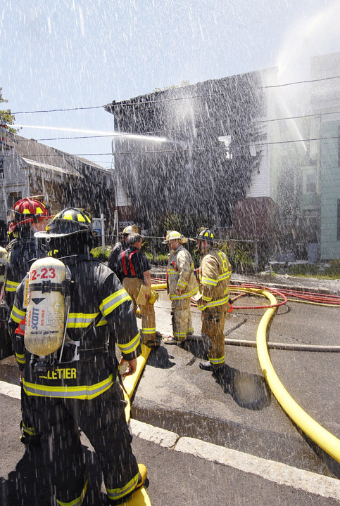 In this May 2009 photo, firefighters pour water onto an apartment building at 8 Kossuth St. in Biddeford that was heavily damaged during a fire that left its occupants homeless. Police say Edna Godin, an occupant at the time, has confessed to starting the fire.
