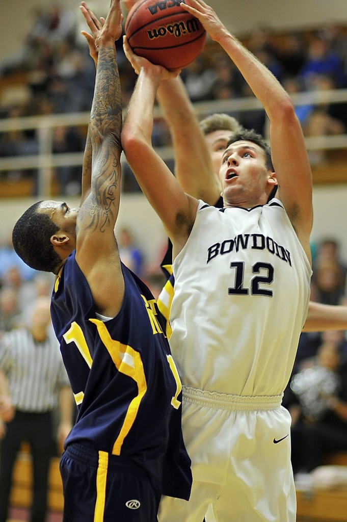 Andrew Madlinger, right, of Bowdoin goes back up with a rebound to score over Southern Maine's Corteze Isaac during a men's basketball game Tuesday night in Brunswick. USM took a 70-68 victory.