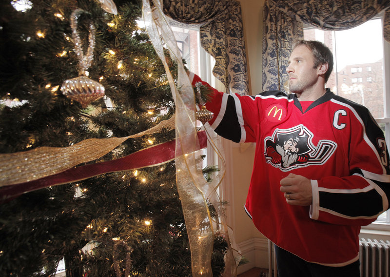 Matt Ellis helps decorate a tree Tuesday at Gary's House, which provides temporary housing for the families of patients receiving treatment in area hospitals, as part of the Portland Pirates' community involvement activities.