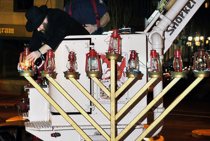 Hampered by gusty winds, Rabbi Moshe Wilansky finally gets his match to keep burning long enough to light a menorah lantern Wednesday night at Portland City Hall plaza. He was lifted up to the candelabrum in the bucket of a fire truck. An additional lantern will be lit each night of Hanukkah until all of them are glowing.