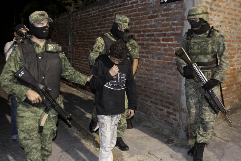 """Mexican army soldiers on Friday escort a 14-year-old suspected of working as a killer for a drug cartel in the city of Cuernavaca, Mexico. """"El Ponchis'' was captured Thursday trying to flee to the U.S. with his 19-year-old sister."""