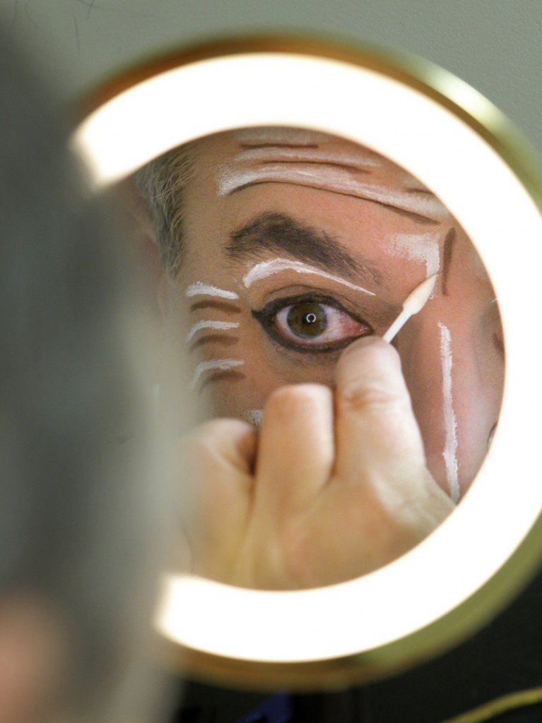 James Herrera applies makeup before taking the stage as Drosselmeyer. The hugely popular show combines the work of hundreds of performers and production staff.