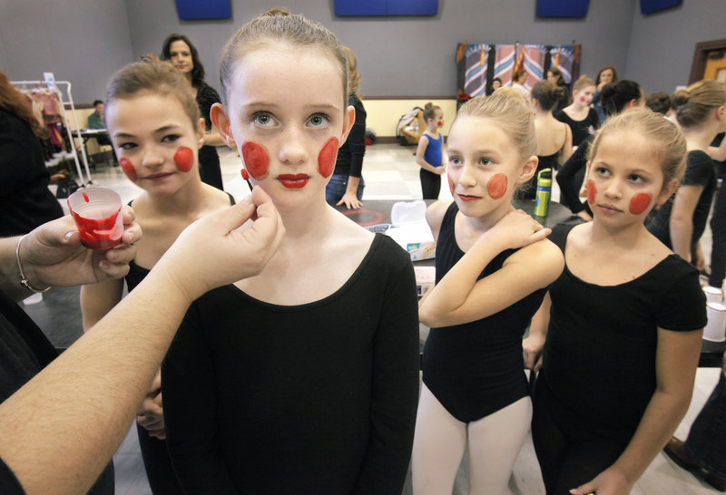 Julia Bisson, left, Erin Bruce and Dorrie Pinchbeck wait and watch as Jill Cass has her toy soldier makeup applied Saturday. The young performers are readied backstage by parents and volunteers in an assembly line-like process.