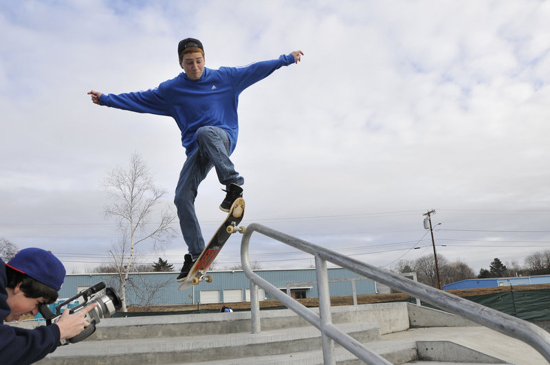 Greyson Gagne, 14, does a board slide as Ryder Salm records the stunt on video. Both are from Conway, N.H.