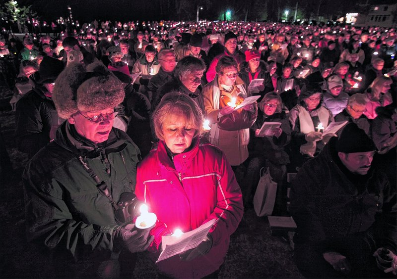"""Bill and Candi Braithwaite of New Hampshire join in on """"The First Noel"""" Saturday night at the Franciscan Monastery in Kennebunk. The caroling and candlelight procession were part of Christmas Prelude."""