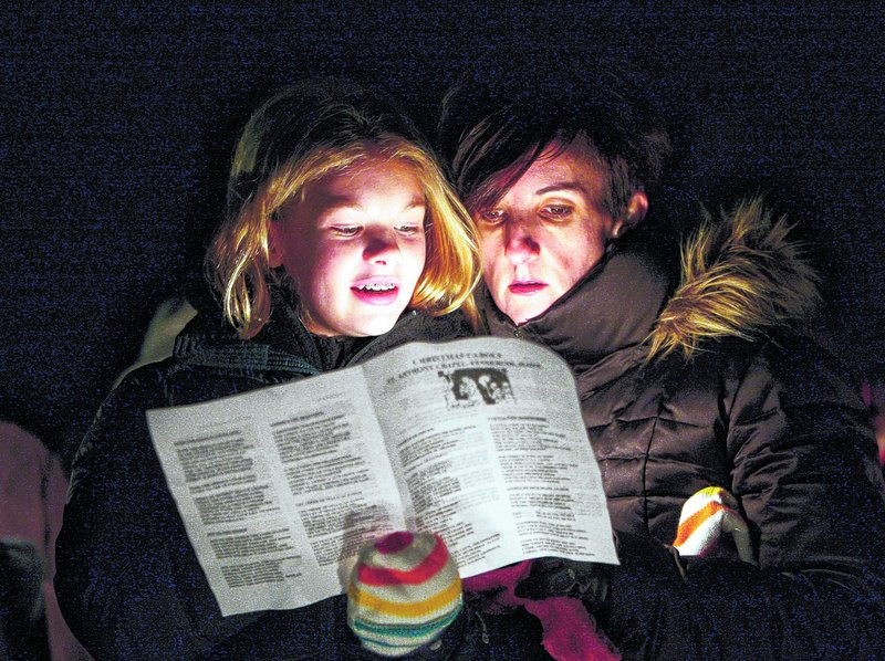 """Amy Catling of York, right, and her daughter Brittany sing """"It Came Upon a Midnight Clear"""" at the Franciscan Monastery in Kennebunk on Saturday night."""