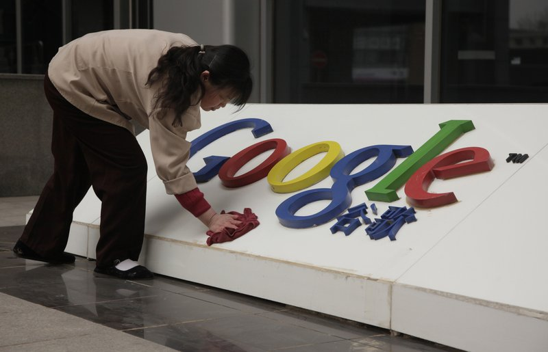 A woman cleans the logo outside the Google China headquarters in Beijing. A leaked cable shows sources told American diplomats that hacking attacks on Google were ordered by China's ruling body.