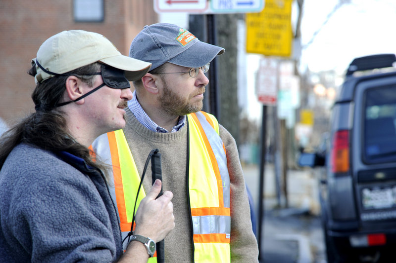Reporter Ray Routhier, right, waits at a street corner with Wayne Lawson of Portland, who is learning how to navigate sidewalks and streets with the help of a cane. Lawson, whose visual impairment can vary, is wearing a sleep mask to simulate blindness.