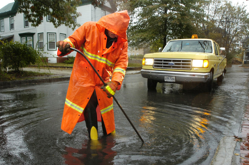 "A city worker unclogs a Beacon Street catch basin after a heavy rain in 2005. Officials think ""storage conduits"" will help."
