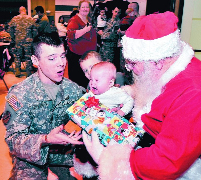 Maine Army National Guard Capt. Eric Dos Santos consoles his daughter Catherine, who cried while sitting on Santa's lap during a Christmas party Sunday at the Waterville Armory.