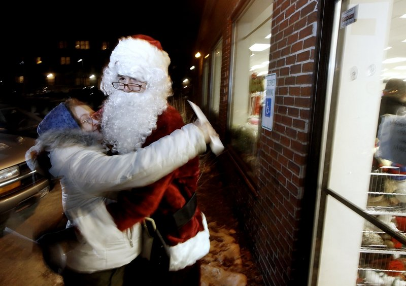 Santa Claus gets a hug from Aurea Parker last year after Parker received $100 at the Goodwill store on Forest Avenue in Portland. The anonymous businessman behind the giveaway is doubling the money and adding locations this year.